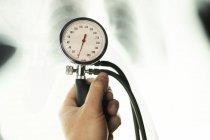 Arzthand mit medizinischem Tonometer vor verschwommenem Röntgenbild — Stockfoto