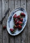 Plate of delicious ripe strawberries on wooden tabletop near metal knife — Foto stock