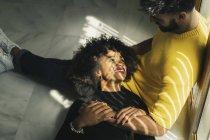 Bella donna afroamericana sorridente che ride sdraiata sulle ginocchia dell'uomo barbuto sul pavimento — Foto stock