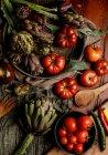 Миски з різних свіжих овочів і серветок серветки на сільському столі в кухні — стокове фото