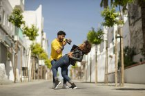 Handsome bearded guy using photo camera to take picture of woman screaming and bending back on city street — Stock Photo