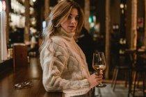 Elegante donna che beve vino mentre si appoggia al bancone nel bar — Foto stock
