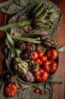 Schüssel mit verschiedenen frischen Gemüse und Stoffservietten auf rustikalem Tisch in der Küche — Stockfoto