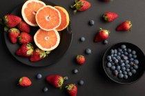 Verschiedene frische Früchte und Beeren auf schwarzem Hintergrund verstreut — Stockfoto