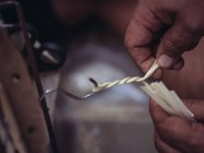Closeup hands of anonymous craftsman using hook for weaving dried palm leaves fiber while working in workshop — Stock Photo