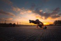 Teenager break dancing in evening park — Stock Photo