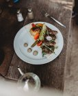 Arabic meat kebab plate with vegetables on plate on wooden table — Foto stock