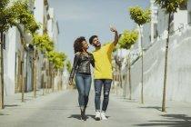 Bello uomo barbuto e bella donna che cammina mentre prende selfie in giornata di sole sulla strada della città — Foto stock