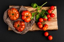 Fresh ripe tomatoes and basil leaves on piece of wood on black background - foto de stock