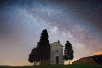 Спокойный пейзаж маленького городка с деревьями в далеком пустом зеленом поле на фоне звездного неба, Италия — стоковое фото