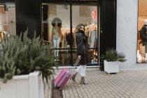 Elegant woman with suitcase walking on street — Stock Photo