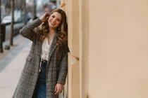 Feliz jovem mulher elegante inclinando-se na parede na rua — Fotografia de Stock