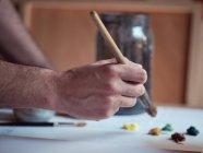 Рука анонимного художника с кистью, рисующей картину на холсте в студии — стоковое фото