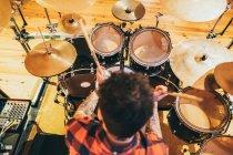Взрослый мужчина, сидящий в музыкальной студии, играет на барабанах — стоковое фото