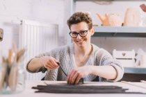 Erwachsene Töpferin legt weichen Tonstreifen auf die Vase, während sie am Tisch in der Werkstatt sitzt — Stockfoto
