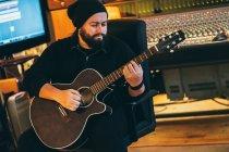 Uomo adulto seduto in studio di musica a suonare la chitarra — Foto stock