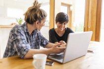 Dos mujeres hermosas y jóvenes desayunando en casa y usando el portátil - foto de stock