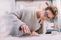 Женщина делает декоративные сердца из мягкой глины на столе в гончарной мастерской — стоковое фото