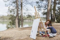Mother and boy painting near lake — Stock Photo