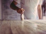 Artista maschio irriconoscibile con pennello che copre tela ruvida con vernice in laboratorio — Foto stock