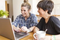 Two beautiful and young women having breakfast at home and using the laptop — Stock Photo