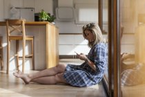 Beautiful and young woman sitting on the floor of her house on the mobile phone — Stock Photo