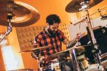 Homem adulto sentado no estúdio de música tocando bateria — Fotografia de Stock