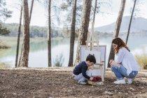 Мама і хлопчик малюють біля озера. — стокове фото