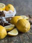 Citrons frais et presse-bois sur la planche en bois — Photo de stock