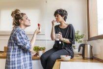 Dos mujeres hermosas y jóvenes desayunando en casa y divirtiéndose, sentadas en la cocina - foto de stock
