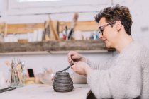 Adult female potter putting soft clay strip on top of vase while sitting at table in workshop — Stock Photo