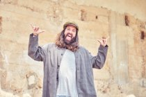 Cheerful and happy stylish bearded man with long hair gesturing on street — Stock Photo