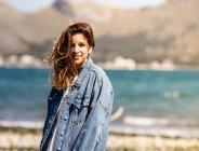Young woman walking on seashore — Stock Photo