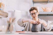 Vaso da vasaio femmina adulto sagomato da morbidi rotoli di argilla mentre si siede a tavola in officina — Foto stock