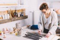 Femme adulte dans des lunettes utilisant une brosse pour couvrir les rouleaux d'argile avec de l'eau tout en travaillant dans un atelier de potier professionnel — Photo de stock