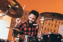 Hombre adulto sentado en el estudio de música tocando la batería - foto de stock