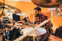 Uomo adulto seduto in studio di musica a suonare la batteria — Foto stock