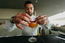 Barman préparant une boisson alcoolisée au bar — Photo de stock