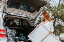 Female artist taking canvas from car — Stock Photo