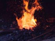 Calentamiento metálico en el antiguo horno herrero sobre carbón en taller tradicional - foto de stock
