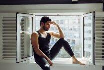Joven hombre exitoso en singlet casual sentado en la ventana y mirando hacia otro lado - foto de stock