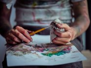 Cropped image of boy in casual clothes smeared in colorful paints sitting on chair and holding brush and napkin — Stock Photo