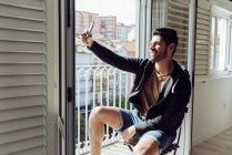 Вид сбоку молодого веселого успешного человека в непринужденной одежде, сидящего на стуле у балкона и делающего селфи со смартфоном — стоковое фото