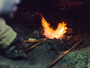 Metal heating in old blacksmith oven on coals in traditional workshop — Stock Photo