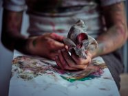 Image recadrée de garçon en vêtements décontractés enduits de peintures colorées assis sur la chaise et tenant brosse et serviette — Photo de stock