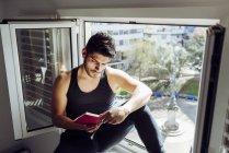 Біля вікна сидить молодий поважний чоловік у звичайній безрукавній сорочці і читає цікаву книжку. — стокове фото