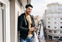 Jeune homme élégant et souriant dans un casque appuyé sur une rampe de terrasse avec smartphone et regardant ailleurs — Photo de stock