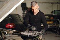 Adulto mecânico masculino em luvas usando ferramentas para fixar veículo na garagem — Fotografia de Stock
