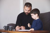 Adult bearded man helping little boy to draw picture while sitting at table at home together — Stock Photo