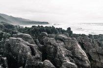 Wasserlandschaft, die an bewölkten Tagen zwischen Klippen im Meer fließt — Stockfoto
